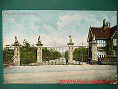 Colourised postcard showing the gates of Hatfield House